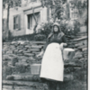 Wife of Curtis Burroughs stands with two pails at the homestead